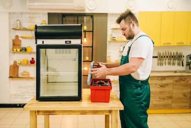 Werknemer met gereedschapskist reparatie koelkast thuis