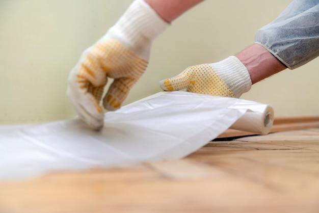 Werknemer met handschoenen en beschermende werkkleding cellofaan plakken.