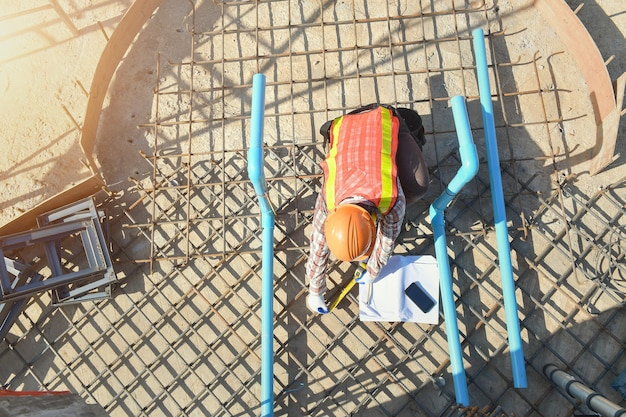 Werknemer met ijzeren constructielijnen voor het bouwen van fundering, bouwvakker