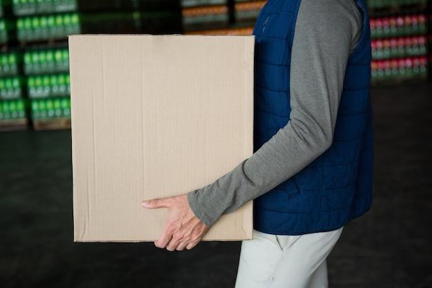 Werknemer met kartonnen doos in magazijn