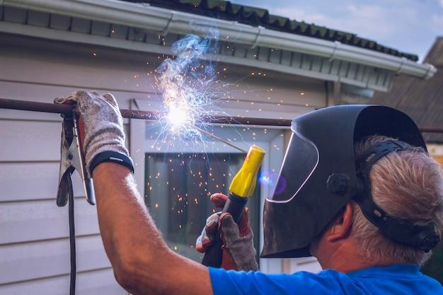 Werknemer met lasapparaat voert werk uit