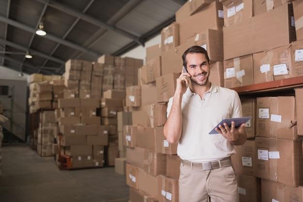 Werknemer met mobiele telefoon en digitale tablet in magazijn