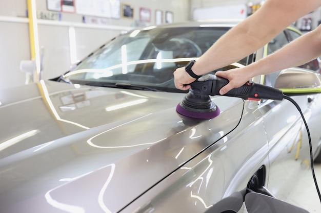 Werknemer met orbitale polijstmachine in auto reparatiewerkplaats auto polijsten en krasverwijdering concept