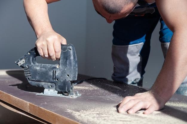 Werknemer met professionele snijgereedschap gesneden houten tafelblad