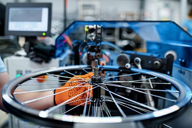 Werknemer met werktuigmachine controleert fietsvelg op speling, fabriek. montage van fietswielen in de werkplaats, installatie van fietsonderdelen