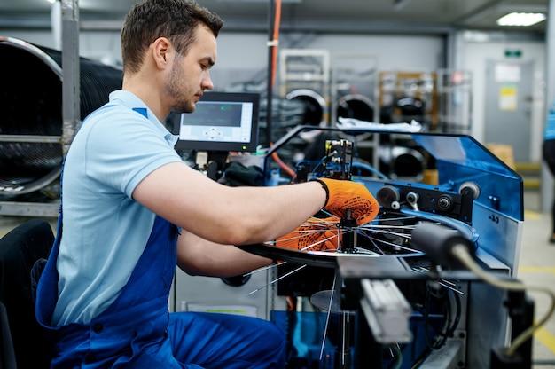 Werknemer met werktuigmachine installeert nieuwe fietsspaken op fabriek. montage fietswielen in werkplaats