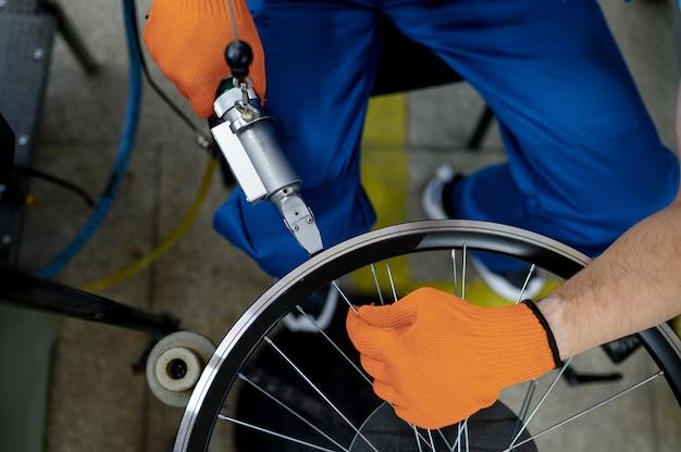Werknemer met werktuigmachine installeert nieuwe fietsvelg op fabriek, bovenaanzicht. montage van fietswielen in de werkplaats, installatie van fietsonderdelen