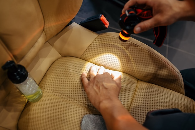 Werknemer met zaklamp controleert autostoel op vuil, chemisch reinigen en detaillering