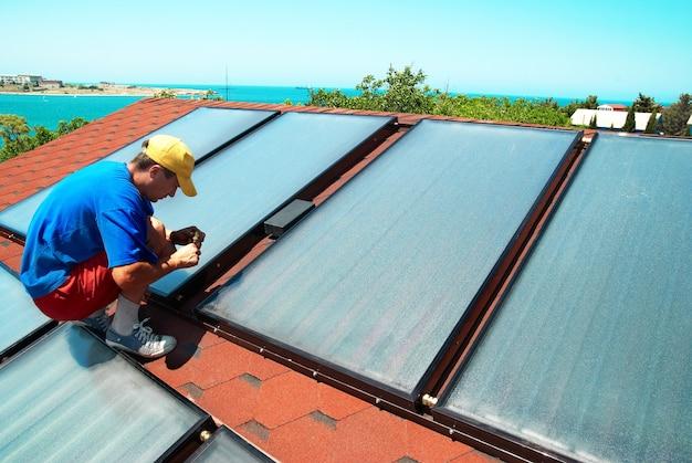 Werknemer montage van zonnepanelen voor waterverwarming op het dak.
