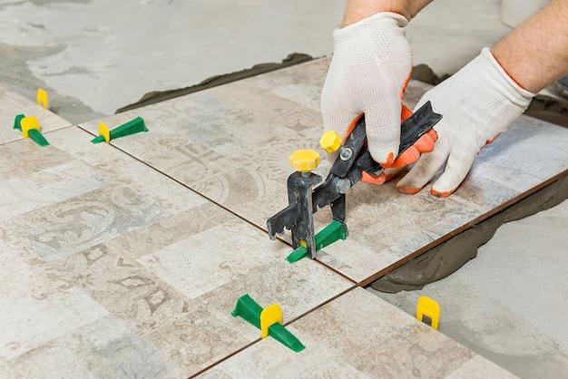 Werknemer nivellering van de keramische tegel met wiggen en clips