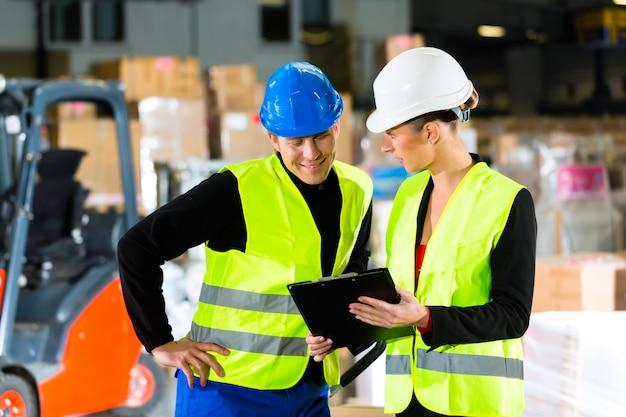 Werknemer of magazijnier en zijn collega met klembord in het magazijn van expeditiebedrijf, wijzend