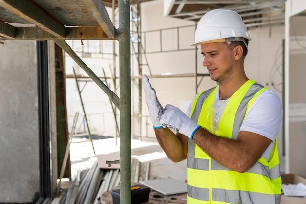 Werknemer op een bouwplaats die beschermingsuitrusting draagt