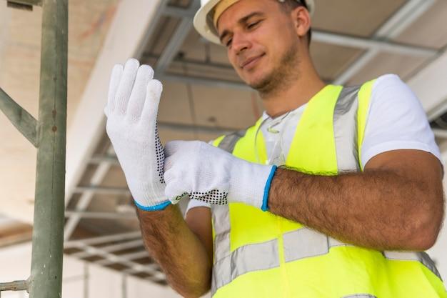 Werknemer op een bouwplaats die handschoenen draagt