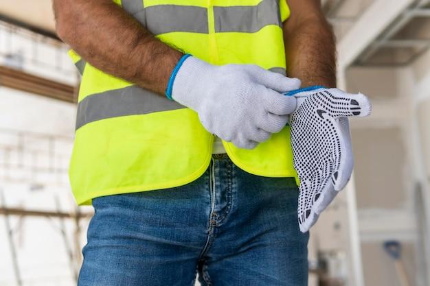 Werknemer op een bouwplaats die handschoenen zet