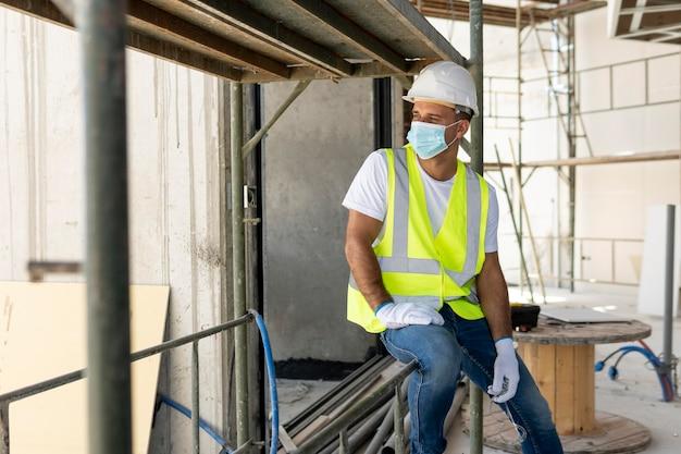 Werknemer op een bouwplaats die medische masker draagt