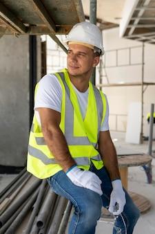 Werknemer op een bouwplaats die veiligheidsuitrusting draagt