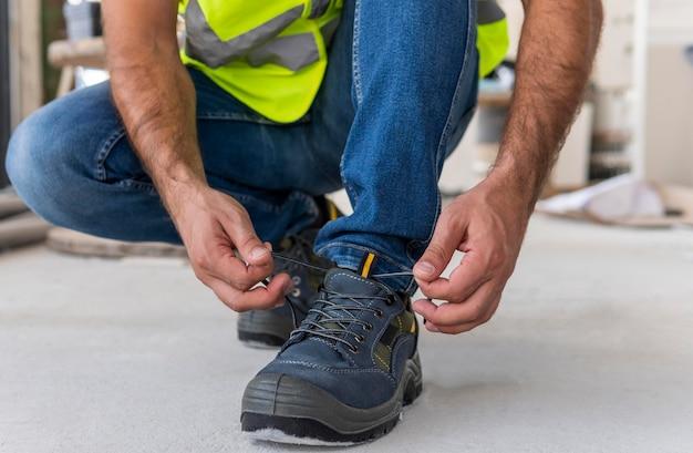 Werknemer op een bouwplaats die zijn schoenen koppelt