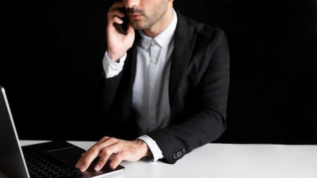 Werknemer op kantoor met behulp van laptop en smartphone