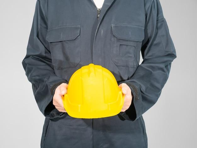 Werknemer permanent in blauwe overall met gele veiligheidshelm geïsoleerd op een grijze achtergrond