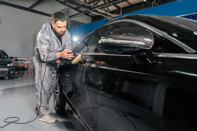 Werknemer polijsten auto met speciale slijper en wax tegen krassen bij het autoservicestation