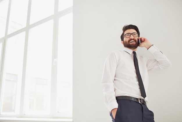 Werknemer praten over de telefoon dicht bij het raam