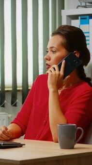 Werknemer praten over de telefoon in zakelijke moderne kantoor. spaanse ondernemer die in een professionele werkruimte werkt, een werkplek in een persoonlijk zakelijk bedrijf dat op een smartphone spreekt en naar het bureaublad van de computer kijkt