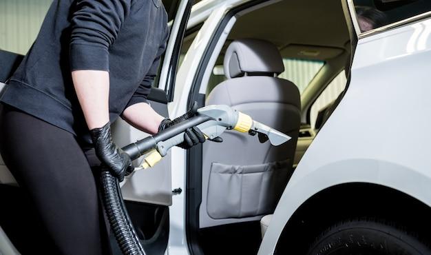 Werknemer reinigt auto-interieur met stofzuiger