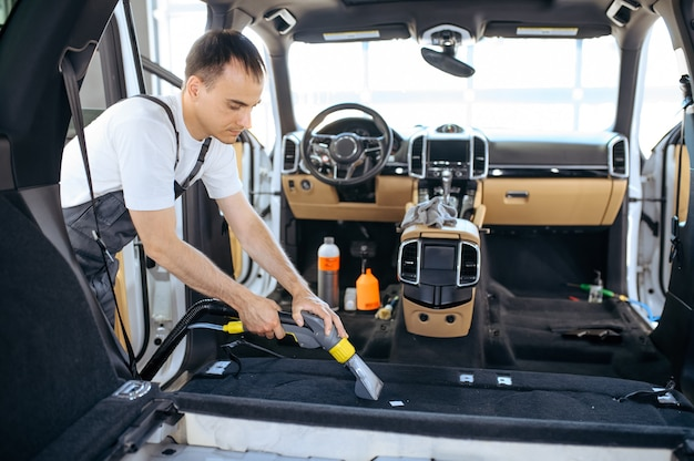 Werknemer reinigt auto-interieurbekleding met stofzuiger, auto stomerij en detaillering