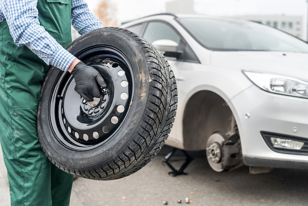 Werknemer reservewiel in de buurt van gebroken auto te houden