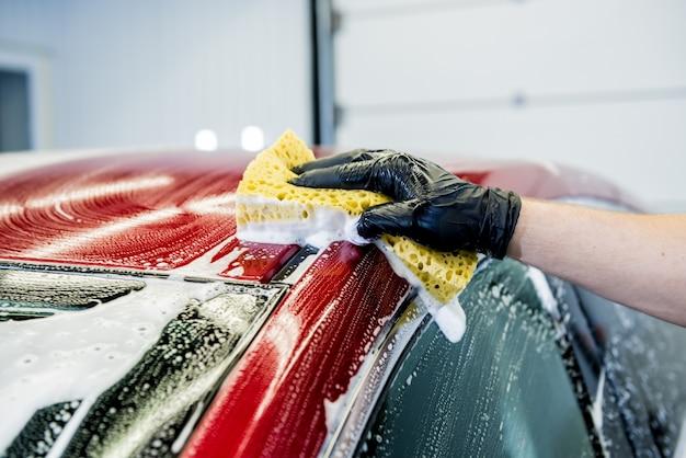 Werknemer rode auto met spons op een wasstraat wassen