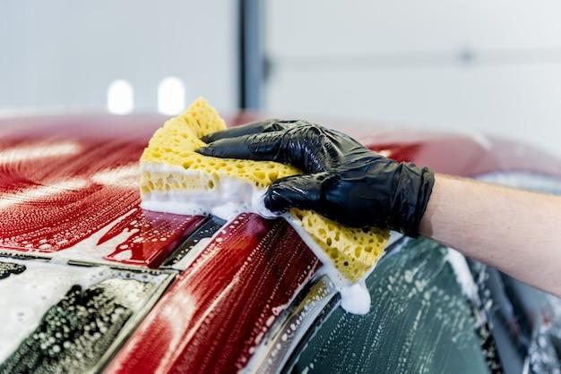 Werknemer rode auto met spons op een wasstraat wassen.
