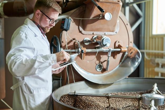 Werknemer roosteren koffie in de fabriek