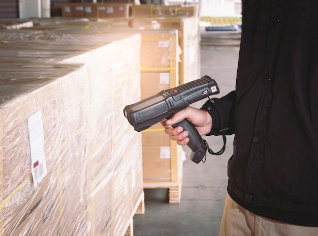 Werknemer scant streepjescodescanner met pakketdozen magazijnvoorraadbeheer