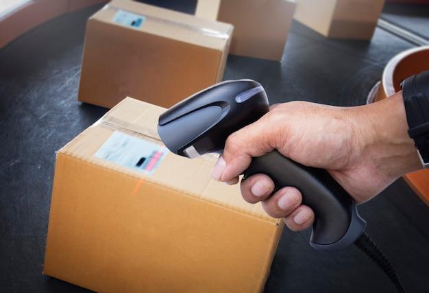 Werknemer scant streepjescodescanner op pakketdozen computer werkhulpmiddelen voor voorraadbeheer