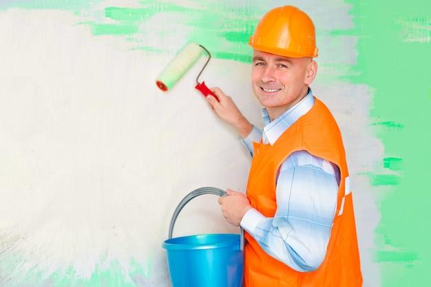 Werknemer schildert een muurroller om te schilderen