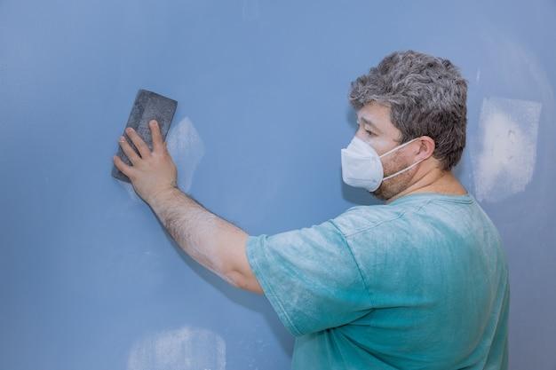 Werknemer schuren van de modder van gipsplaten met zand troffel tijdens de renovatie van het huis op kamer