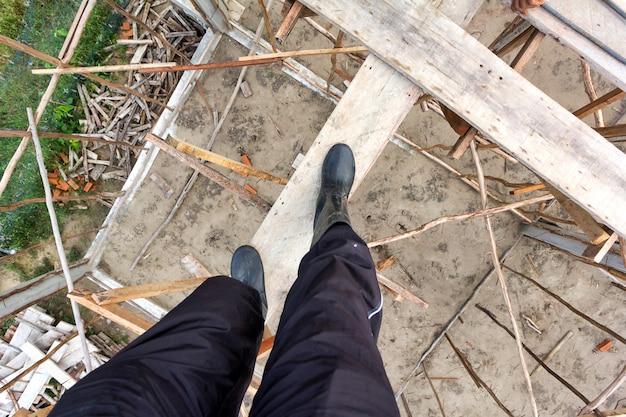 Werknemer slijtage boot staan op houten steigers op de bouwplaats.