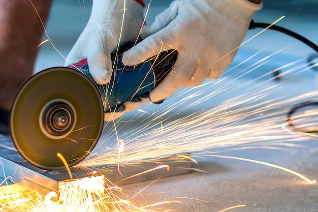 Werknemer snijden metaal met grinder.