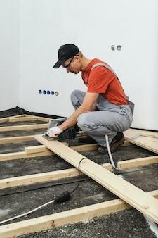 Werknemer snijdt houten vloerplanken.