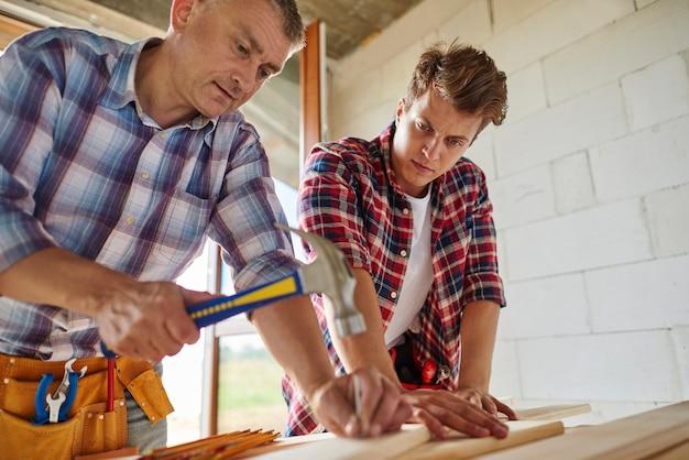 Werknemer spijker in houten plank steken