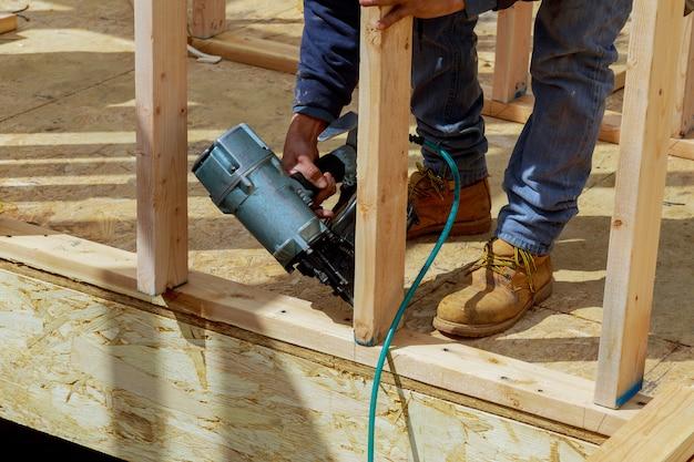 Werknemer spijkeren hout met lucht nagelpistool