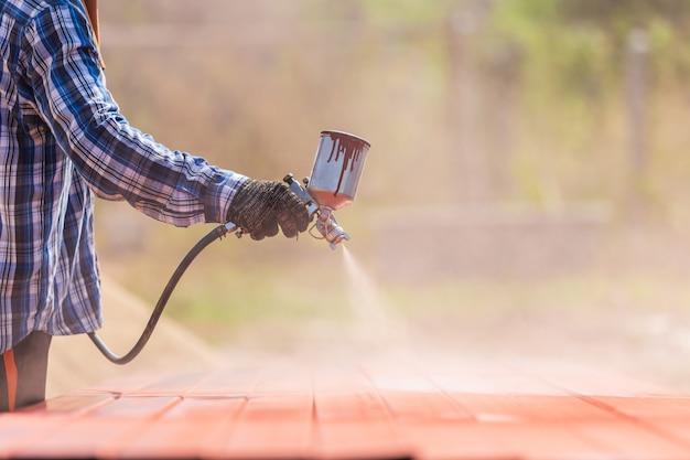 Werknemer spuit verf op stalen buis om roest op het oppervlak te voorkomen