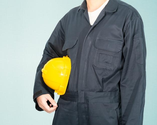 Werknemer staande in blauwe overall met gele veiligheidshelm geïsoleerd op blauwe achtergrond Premium Foto