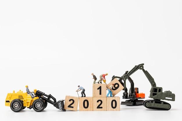 Werknemer team minatures maken houten blok met nummer 2020