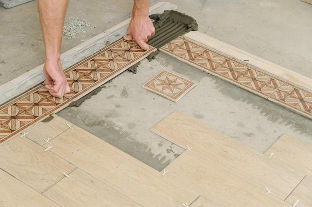 Werknemer tegels op de vloer zetten.