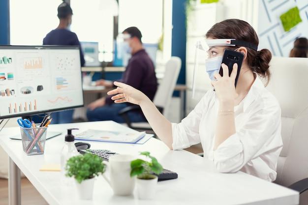 Werknemer tijdens wereldwijde pandemie met gezichtsmasker met uitleg over financiële grafiek tijdens telefoongesprek. multi-etnische collega's die werken met respect voor sociale afstand in een financieel bedrijf.
