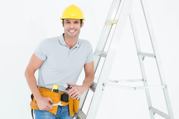 Werknemer tools te houden terwijl leunend op stap ladder