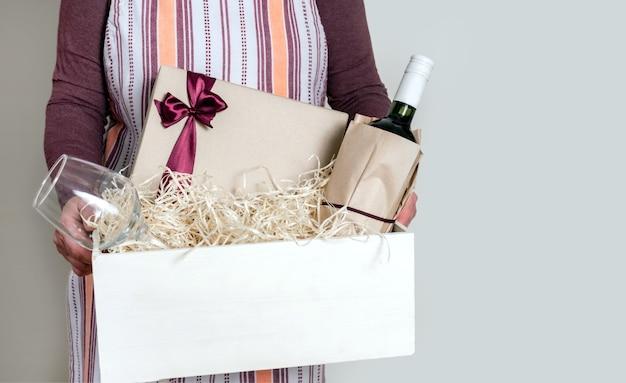 Werknemer van bezorgservice die fles wijn en geschenken inpakken in doos met rietje voor klant.