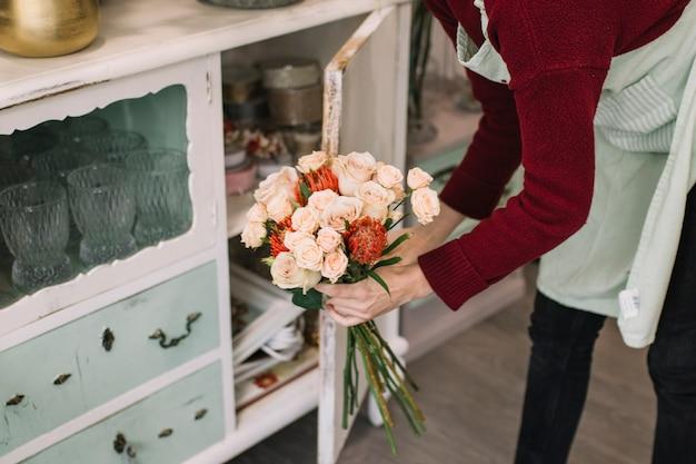 Werknemer van bloemenwinkel met boeket