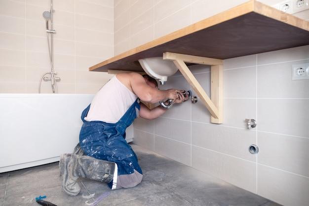 Werknemer van de close-up de mannelijke loodgieter in blauw eenvormig denim, overall, bevestigende gootsteen in badkamers met tegelmuur. professionele sanitairreparatieservice, installatie waterleidingen, man gemonteerde rioolafvoer